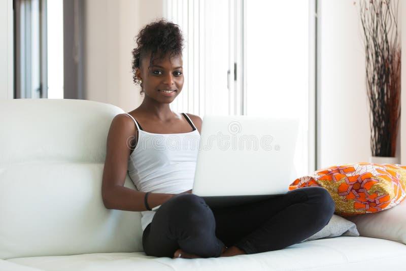 Muchacha afroamericana del estudiante que usa un ordenador portátil - el PE negro fotos de archivo libres de regalías