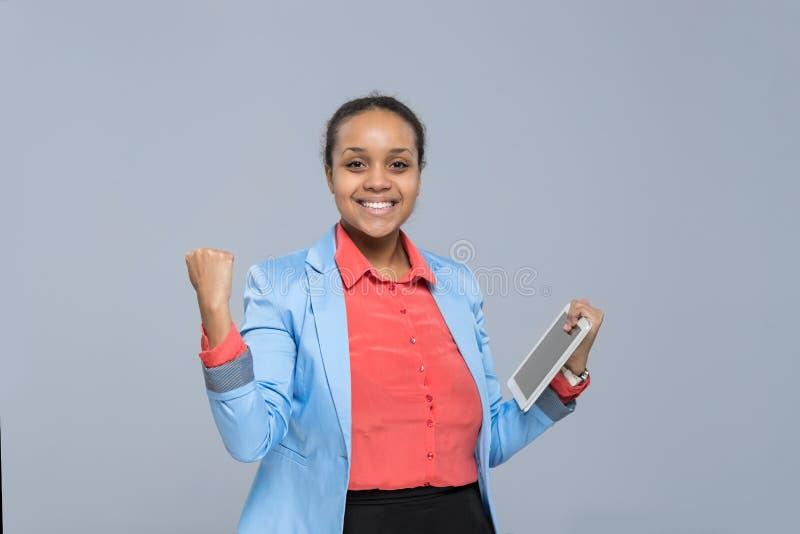 Muchacha afroamericana emocionada de negocios de la mujer de la tableta joven feliz del control imágenes de archivo libres de regalías