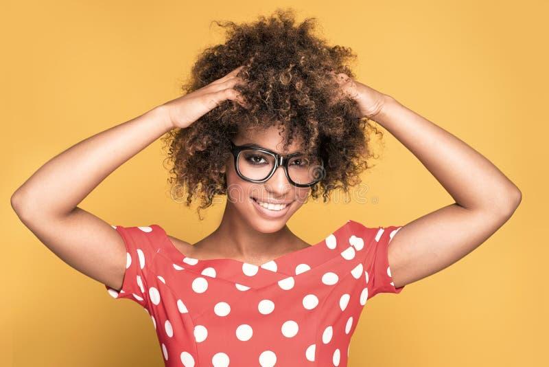Muchacha afroamericana en lentes en fondo amarillo foto de archivo