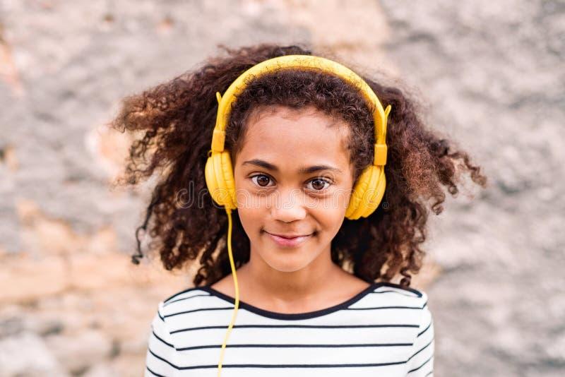 Muchacha afroamericana hermosa con los auriculares, música que escucha fotografía de archivo