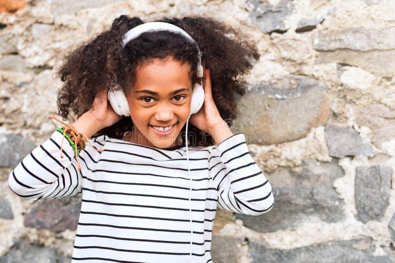 Muchacha afroamericana hermosa con los auriculares, música que escucha fotografía de archivo libre de regalías