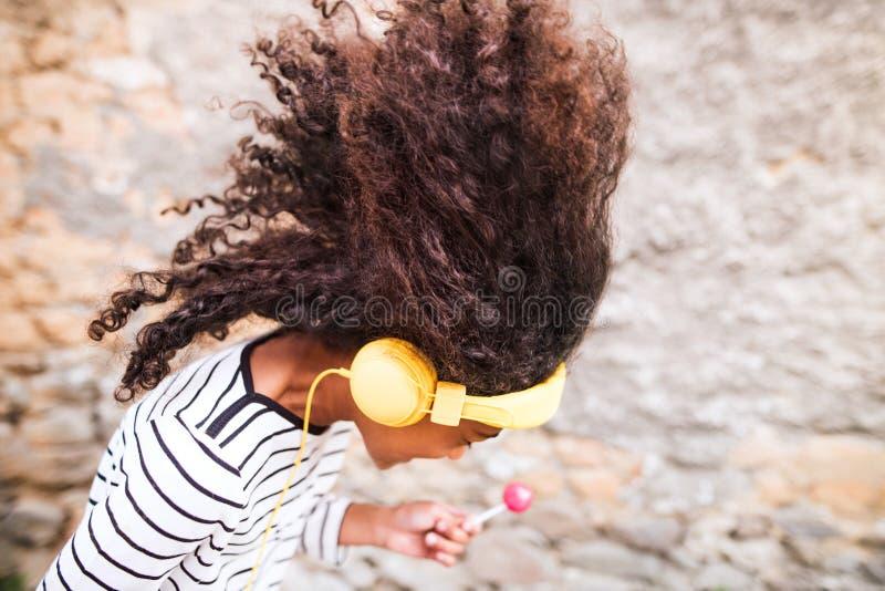 Muchacha afroamericana hermosa con los auriculares, música que escucha imagen de archivo libre de regalías