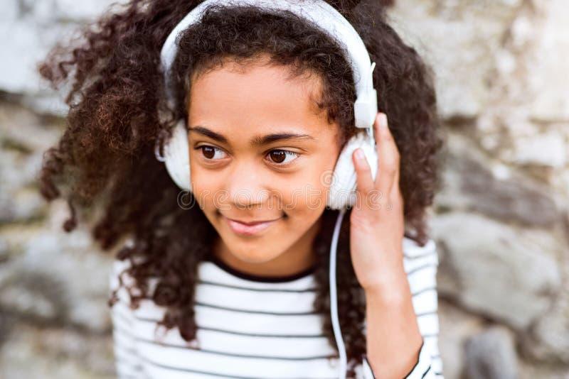 Muchacha afroamericana hermosa con los auriculares, música que escucha imagenes de archivo