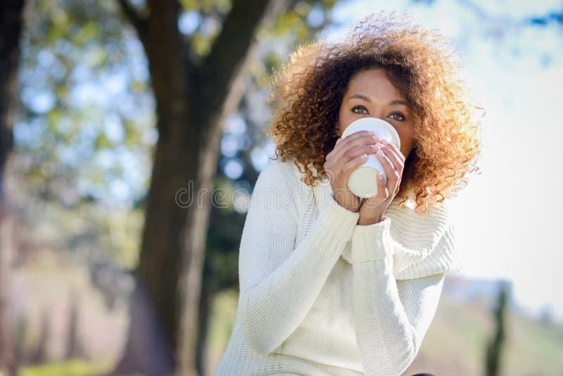 Muchacha afroamericana joven con el peinado afro con la taza de café fotografía de archivo