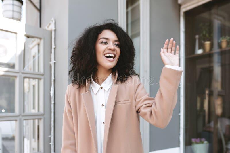 Muchacha afroamericana joven que sonríe y que muestra hola gesto en muchacha alegre de la calle en capa beige y la camisa blanca imagen de archivo libre de regalías