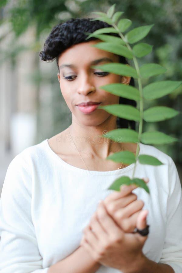 Muchacha afroamericana negra que se coloca con la hoja verde, teniendo blusa blanca de las explosiones y el llevar fotos de archivo