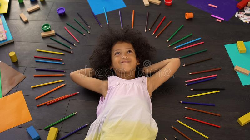 Muchacha afroamericana preescolar rizada linda en piso que piensa en días de fiesta imagen de archivo