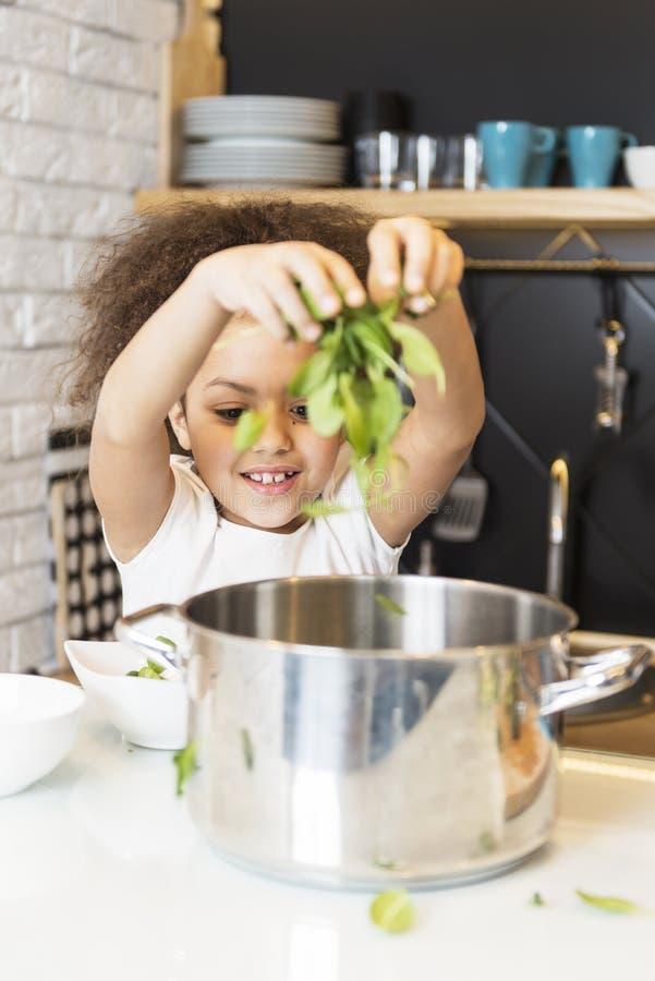 Muchacha afroamericana que cocina en la cocina fotos de archivo