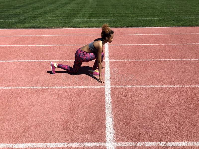 Muchacha afroamericana que consigue lista para comenzar a correr foto de archivo