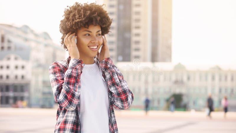 Muchacha afroamericana sonriente en auriculares que disfruta de la música en la calle, relajación imagen de archivo