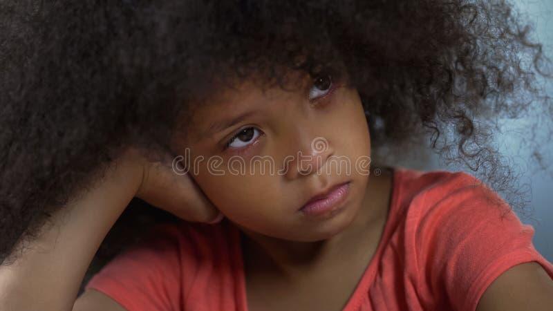 Muchacha afroamericana triste sola que se sienta en la tabla, racismo y bulling en la escuela fotos de archivo libres de regalías