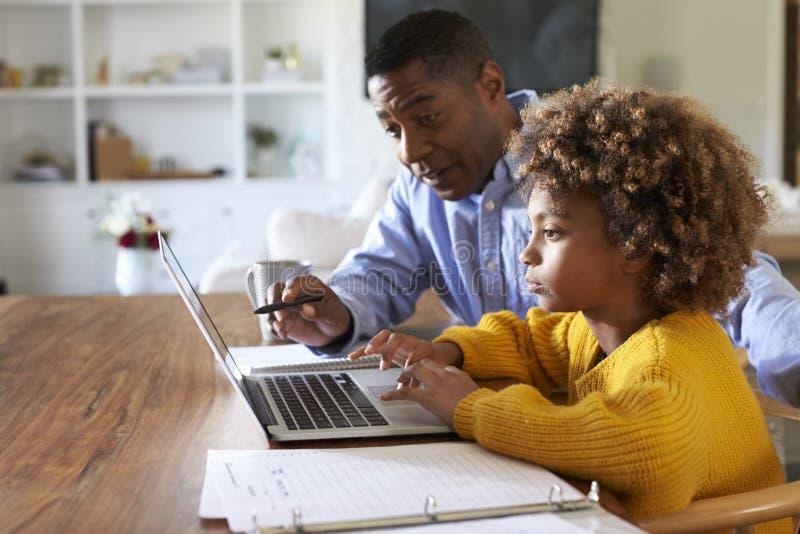 Muchacha afroamericana usando un ordenador portátil que se sienta en la tabla en el comedor con su profesor particular casero, FO fotografía de archivo libre de regalías