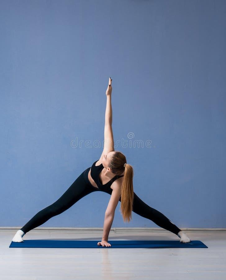 muchacha agradable en un cuarto encendido de la yoga que hace ejercicios imagen de archivo libre de regalías