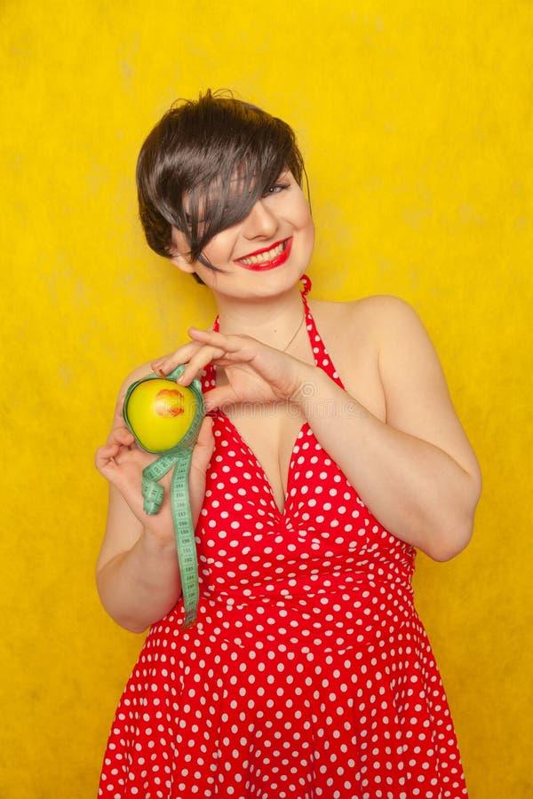 Muchacha agradable encantadora en un vestido retro rojo con los lunares listos para la pérdida de peso del verano, ella está llev fotos de archivo