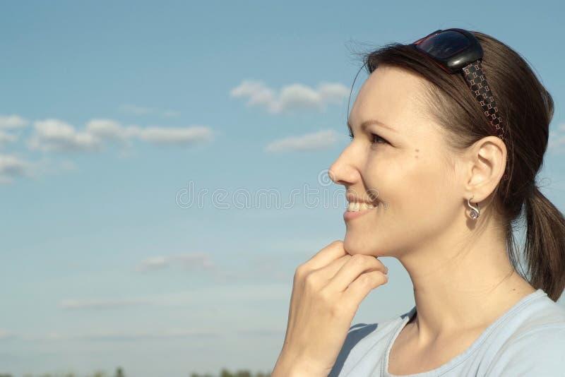 Muchacha agradable feliz contra el cielo imagen de archivo libre de regalías