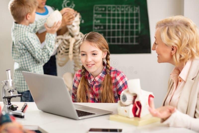 Muchacha agradable feliz que mira la pantalla del ordenador portátil foto de archivo