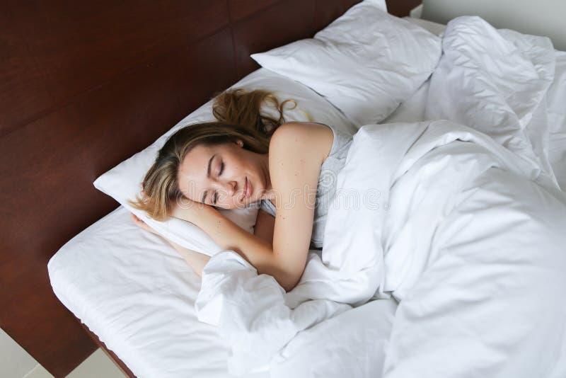 Muchacha agradable joven que duerme por mañana en cama de madera con los linos blancos imágenes de archivo libres de regalías