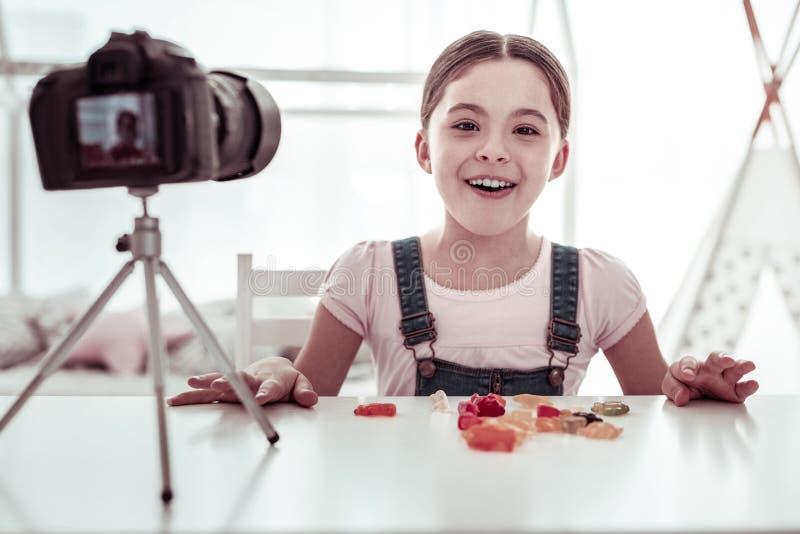 Muchacha agradable positiva feliz que come osos gomosos imagen de archivo