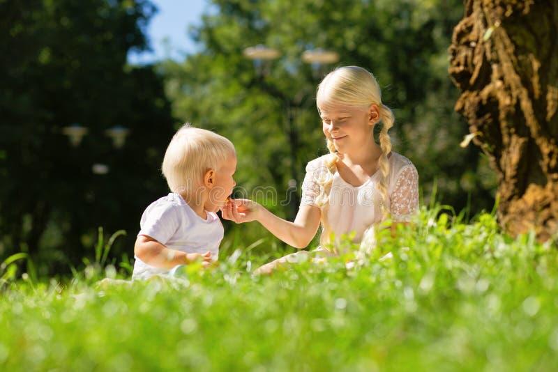 Muchacha agradable que alimenta a un pequeño muchacho con una torta fotos de archivo