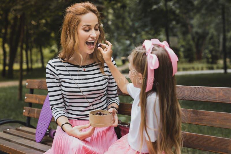 Muchacha agradable que cuida que da a caramelo dulce su madre fotografía de archivo libre de regalías