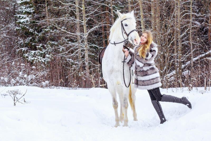 Muchacha agradable y caballo blanco al aire libre en un invierno foto de archivo
