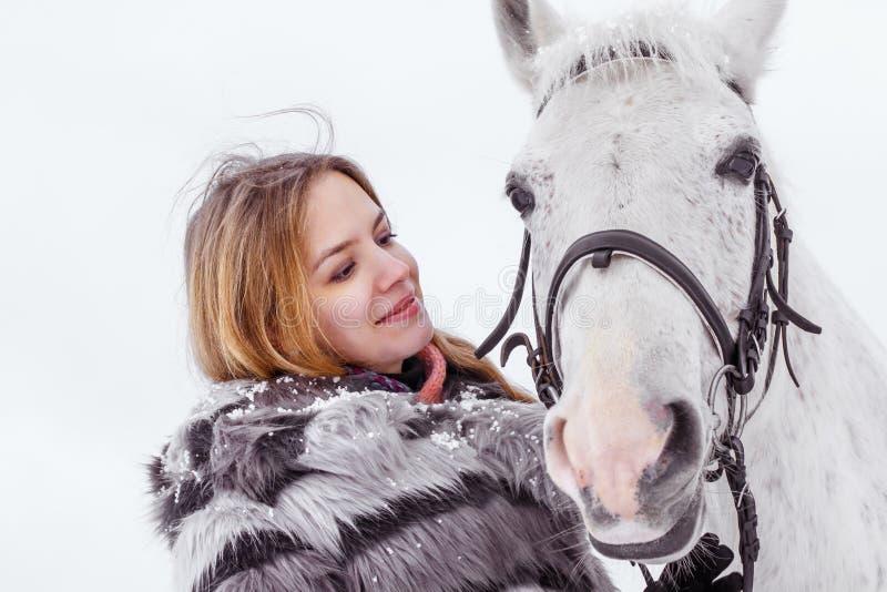 Muchacha agradable y caballo blanco al aire libre en un invierno fotos de archivo