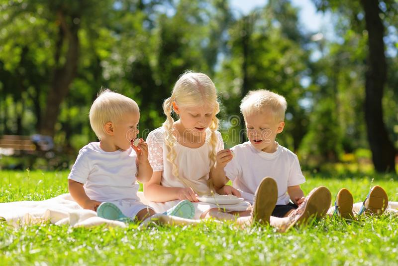 Muchacha agradable y muchachos que se sientan en el parque todo junto imagen de archivo libre de regalías