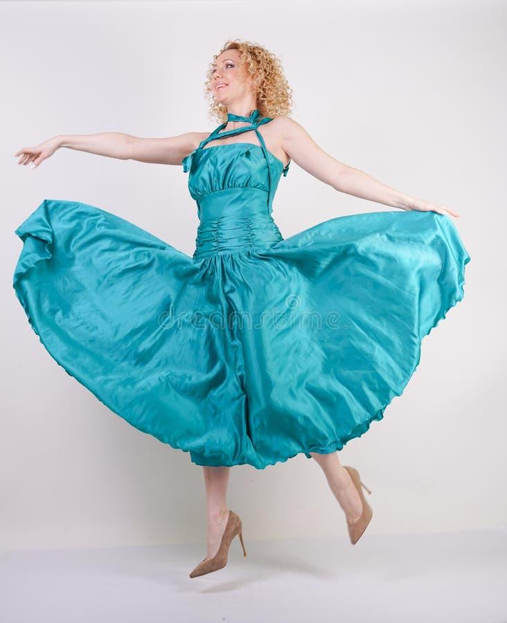 Muchacha airosa delgada en volar el vestido de noche azul en el fondo blanco en estudio imagen de archivo