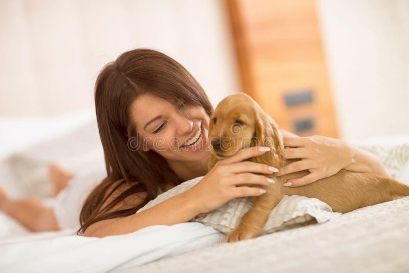 Muchacha alegre con el perrito bonito que miente en cama imagenes de archivo