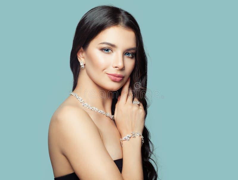 Muchacha alegre con el retrato de la joyería Mujer morena con maquillaje, pelo permed y el collar de diamantes fotos de archivo