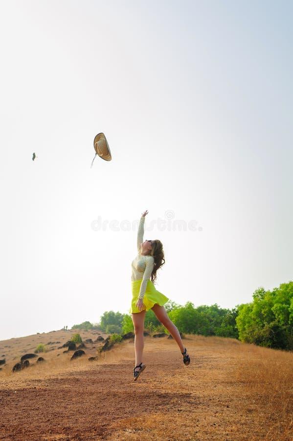 Muchacha alegre con el sombrero de paja largo de los saltos y de los tiros del pelo en el aire Mujer morena joven en paseos de la imágenes de archivo libres de regalías