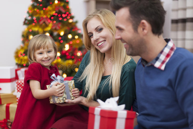 Muchacha alegre con los padres en tiempo de la Navidad imagen de archivo libre de regalías