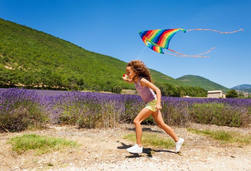 Muchacha alegre del preadolescente que corre con la cometa del arco iris fotos de archivo
