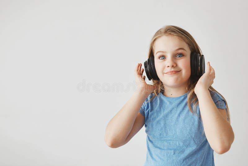 Muchacha alegre divertida con el pelo ligero y los ojos azules, auriculares que llevan mirada in camera con la expresión chocada  foto de archivo
