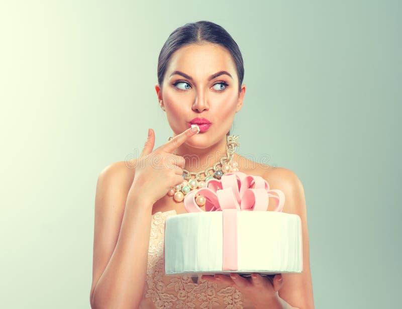 Muchacha alegre divertida del modelo de la belleza que sostiene la torta hermosa grande del partido o de cumpleaños imagenes de archivo