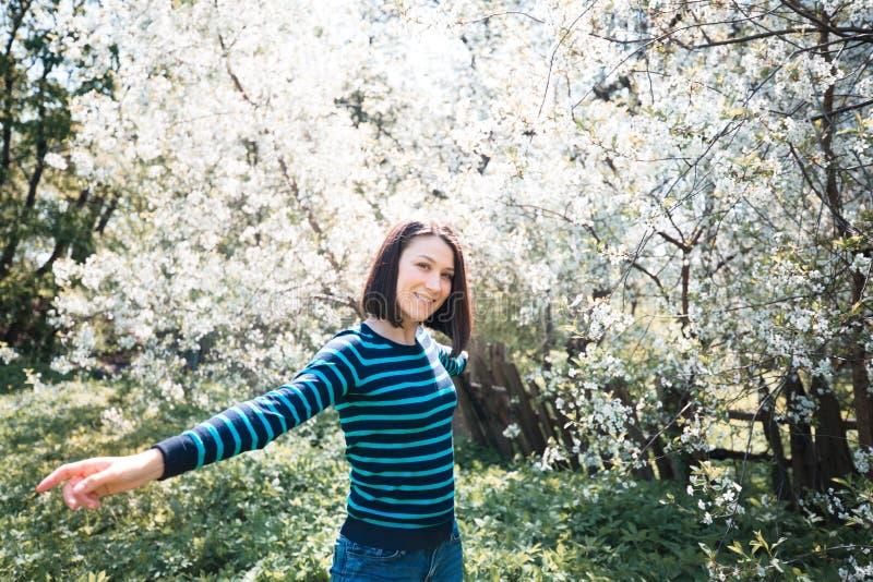 Muchacha alegre en jardín floreciente Humor del resorte Mujer joven asoleada fotos de archivo