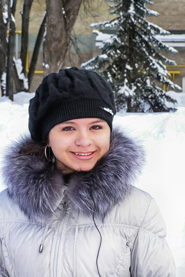 Muchacha alegre en la nieve en un fondo de árboles fotos de archivo