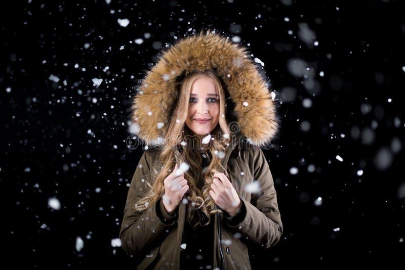 Muchacha alegre en nieve en un fondo negro imágenes de archivo libres de regalías