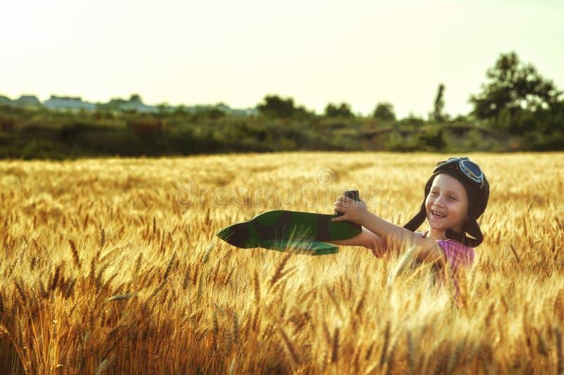 Muchacha alegre en un campo del trigo que juega con un avión modelo imagen de archivo libre de regalías