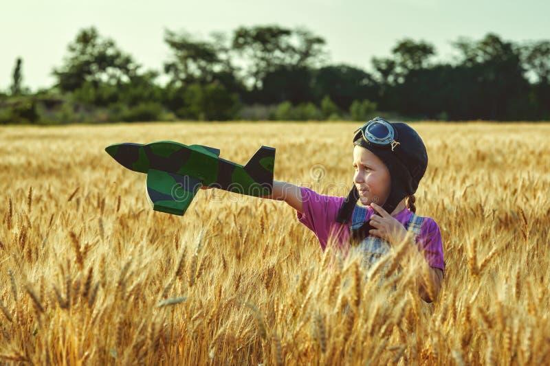 Muchacha alegre en un campo del trigo que juega con un avión modelo imagen de archivo