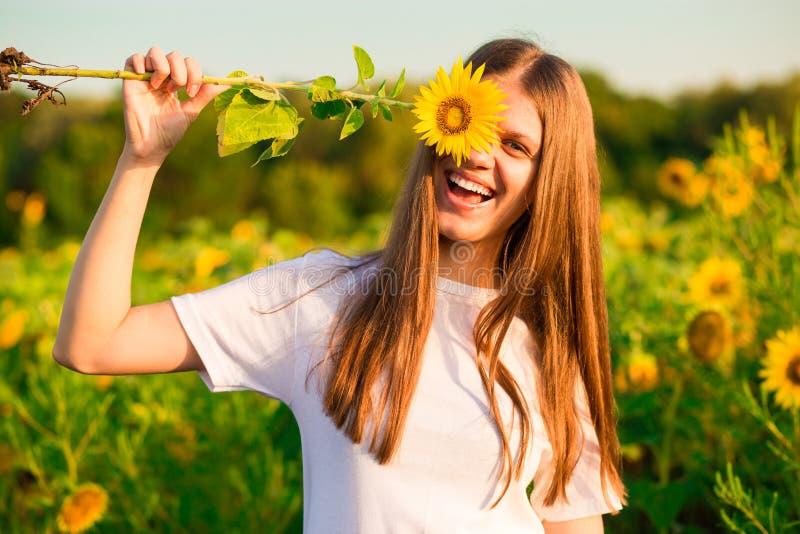 Muchacha alegre feliz con el girasol que disfruta de la naturaleza y de la risa fotografía de archivo