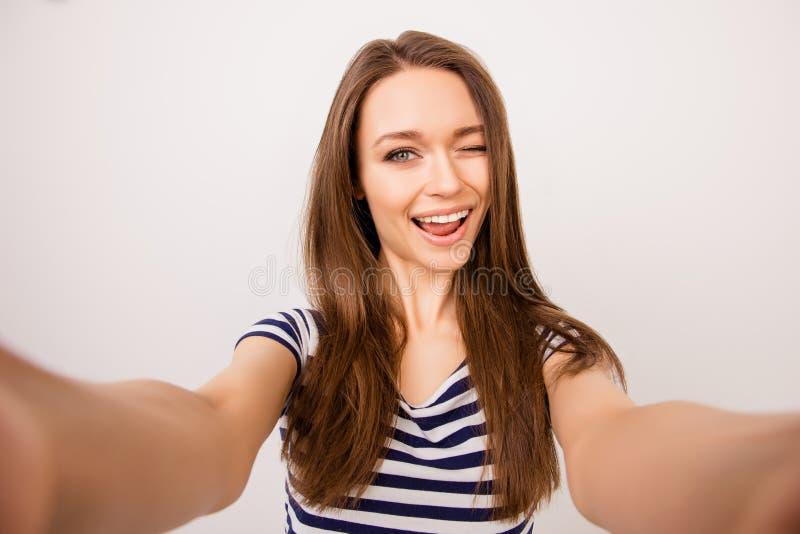 Muchacha alegre joven en la camiseta rayada que toma el selfie y el guiño fotos de archivo