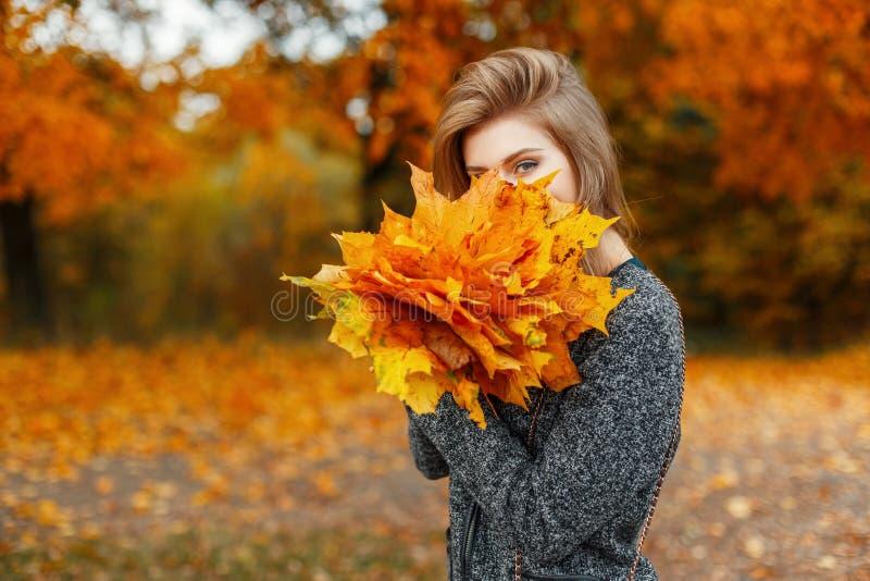 Muchacha alegre joven hermosa con caminar de las hojas de otoño fotografía de archivo