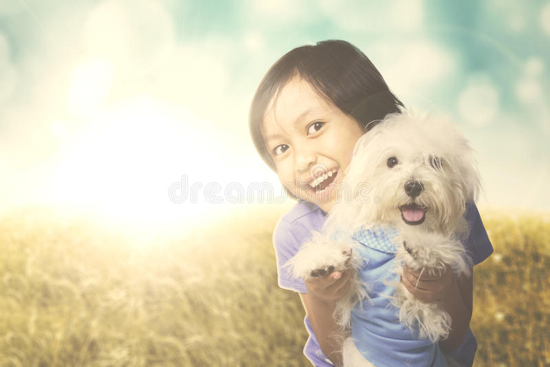 Muchacha alegre que abraza un perro maltés fotografía de archivo
