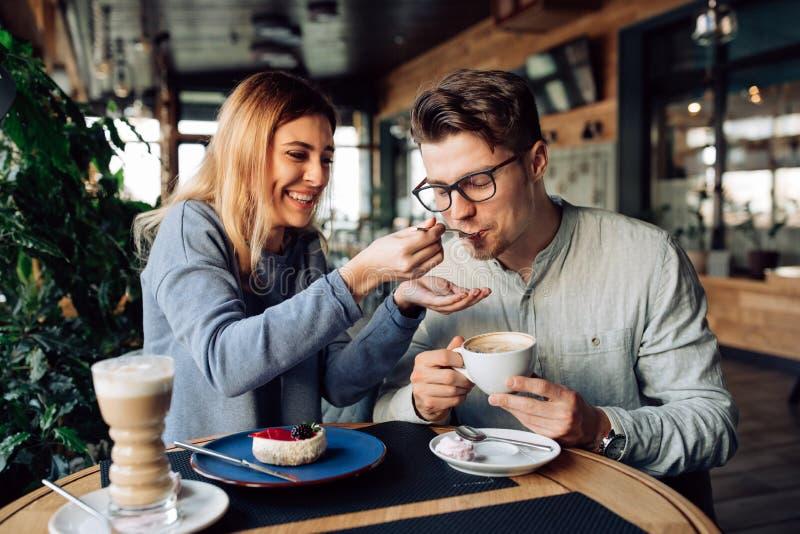 Muchacha alegre que alimenta a su novio, mientras que descansa en el café fotos de archivo libres de regalías