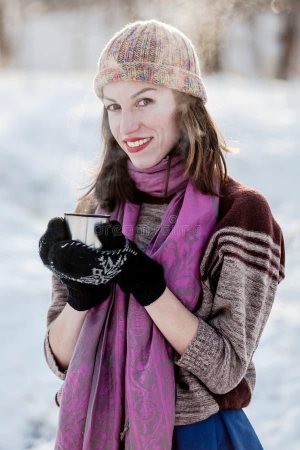 Muchacha alegre que bebe té caliente con el vapor al aire libre imagen de archivo