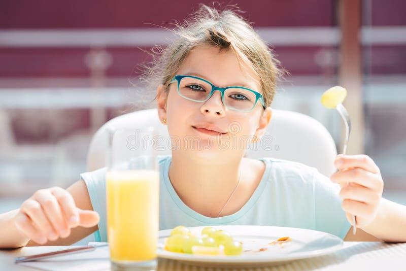 Muchacha alegre que come las crepes, fruta fresca y bebiendo el zumo de naranja durante forma de vida sana del desayuno, dieta ve fotos de archivo