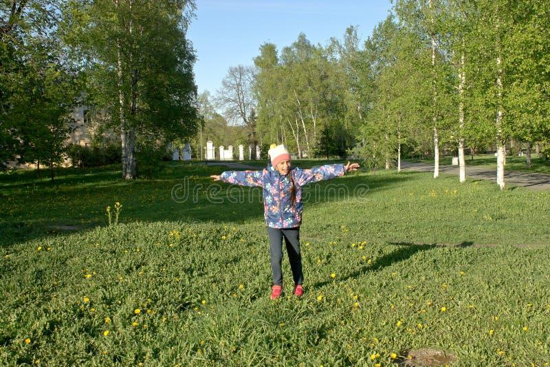 Muchacha alegre que corre a través de la hierba en un día soleado agradable imagen de archivo libre de regalías