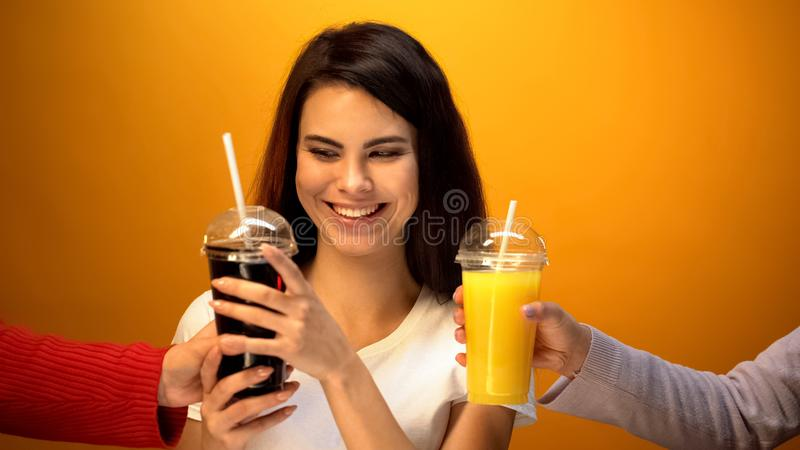 Muchacha alegre que elige soda en vez del zumo de naranja, apego a las bebidas dulces fotos de archivo