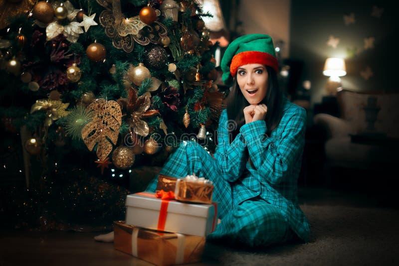 Muchacha alegre que encuentra una pila de presentes debajo de su árbol de navidad imagenes de archivo